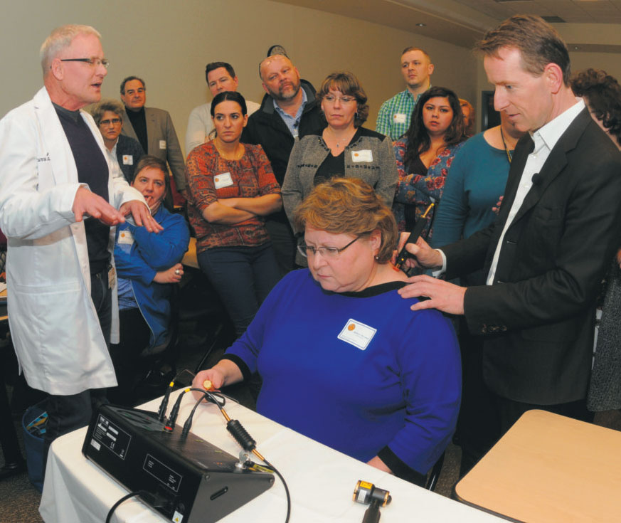 Dr. Robert Bowen, left, describes PBM therapy while James Carroll, founder and CEO of THOR Photomedicine demonstrates how the therapy works on Barbara Sherman's neck during an interactive training course Wednesday, at Shepherd University.